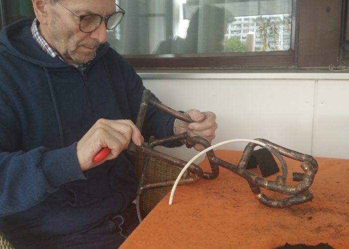 Demenzbetreuung selbstbestimmt ermutigt und fördert Menschen mit Demenz, wie diesen Senior, der mit einem Werkzeug an einem Metallgegenstand arbeitet.